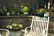 A pair of white wrought-iron chairs in an outdoor space
