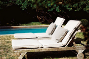 A pair of wooden outdoor chaises beside a pool