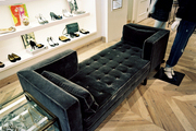 A two-sided tufted bench beside a display of shoes