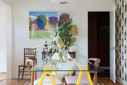 An eclectic dining space with a striped rug.