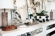 A white dresser topped with mirrors and leopard-print lamps