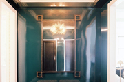 A gold ceiling and lacquered blue walls in an entryway