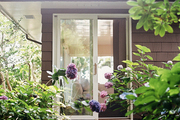 Sliding patio doors leading to a wooden deck surrounded by hydrangeas