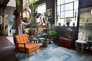 An eclectic living space with an orange chair.