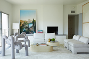 A living room with matching white sofas and abstract seating chairs.