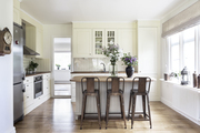Off-white traditional kitchen with large window.