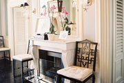 Black fretwork chairs on either side of a marble mantel