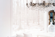 A crystal chandelier paired with a white couch and pillows