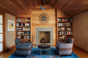 Brown and blue wood-lined living room with bookshelves.