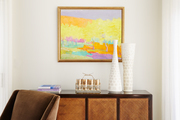 A midcentury style brown wooden credenza sits below a modern bright landscape painting.