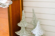A trio of trees on the ground next to a credenza.