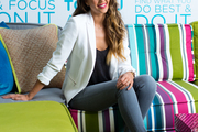 Jessica Alba on a multicolored sofa at her Honest Company office
