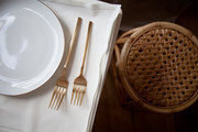Gold flatware next to a rattan stool