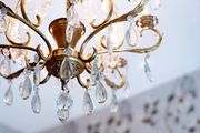 A crystal-and-gold chandelier in a room with floral wallpaper