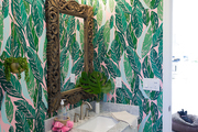 A bathroom with pink and green leaf wallpaper.