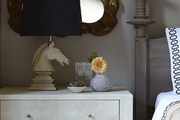 Sculpture-based Lamp and small vase atop white nightstand with drawers.
