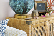 A table lamp atop a rattan cabinet in a living room