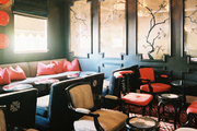 A series of framed chinoiserie panels above pink and gray chairs