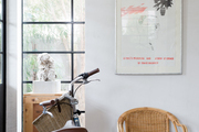 A David Hockney piece hangs above a rattan chair and bike.