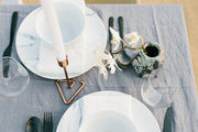 A dining table with a gray table cloth and black flatware.