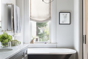 Contemporary bathroom with clawfoot tub and modern light fixture.