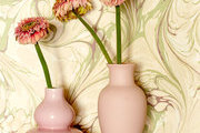Two pink ceramic vases in the marble wallpapered bath of a New Orleans home