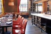 Red lacquered schoolhouse chairs in a restaurant space