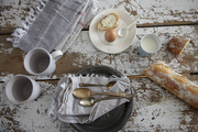 A table set for breakfast with linens, silverware, and ceramics by Odette Williams.