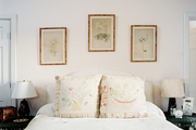A trio of botanical prints hung above a bed