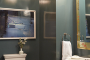 Large scale framed art hanging above toilet in green walled bathroom.