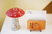 A mushroom figurine and a letter holder on a white tabletop