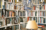 A beaded chandelier above a wooden desk surrounded by books