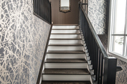 A staircase surrounded by gold and gray wall treatment.