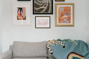 A living space with abstract art decor and decorative throw blanket sitting above the sofa.