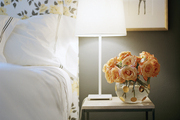 A floral upholstered headboard contrasted with black walls