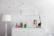Text light-box above a mirrored dresser with small colorful decor.