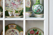 Antique Minton china on display in a white china cabinet