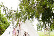 A teepee under a large pine tree
