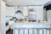 White kitchen with marble countertops and modern stools.