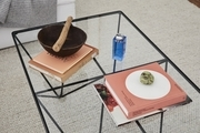 A detail shot of a glass coffee table with coffee table books and objects.