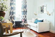 A white couch, blue ikat curtains, and nesting tables in a living space