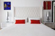 A guest suite with colorful artwork and a wingback headboard