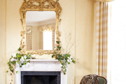 Greenery and flowers arranged atop a white mantel