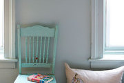 A weathered turquoise chair near an equestrian pillow