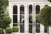 Boxwoods in white planters in a courtyard