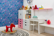 A bright and colorful playroom with blue wallpaper.