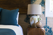 Wooden accents add a rustic vibe in a blue and tan guest room