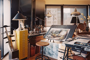An artist's studio with a pair of floor lamps and a mirrored folding screen