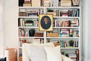 Framed art layered in front of a white bookcase