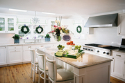 White cabinets and an island in a kitchen decorated for the holidays